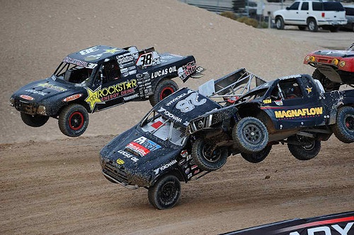 <img src= &quot;racing_pro_lite_trucks.jpg&quot; alt= &quot;pro lite trucks catch air and bump as they race toward the finish line&quot;