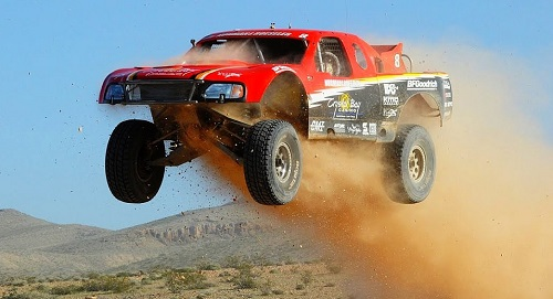 "<img src= trophy_truck.jpg"" alt= ""red trophy truck catches big air"" />"